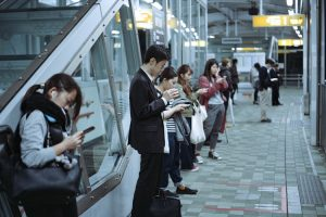 People looking at mobile phones on train platform