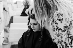 Female hairdresser cutting hair of female client