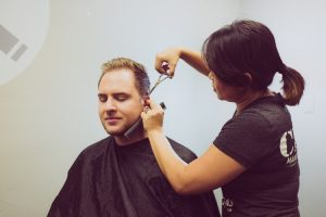 Female cutting male client hair