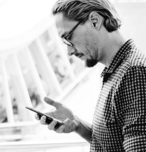 Man standing looking at smartphone