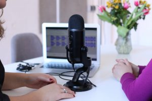 Two women recording podcast in front of laptop